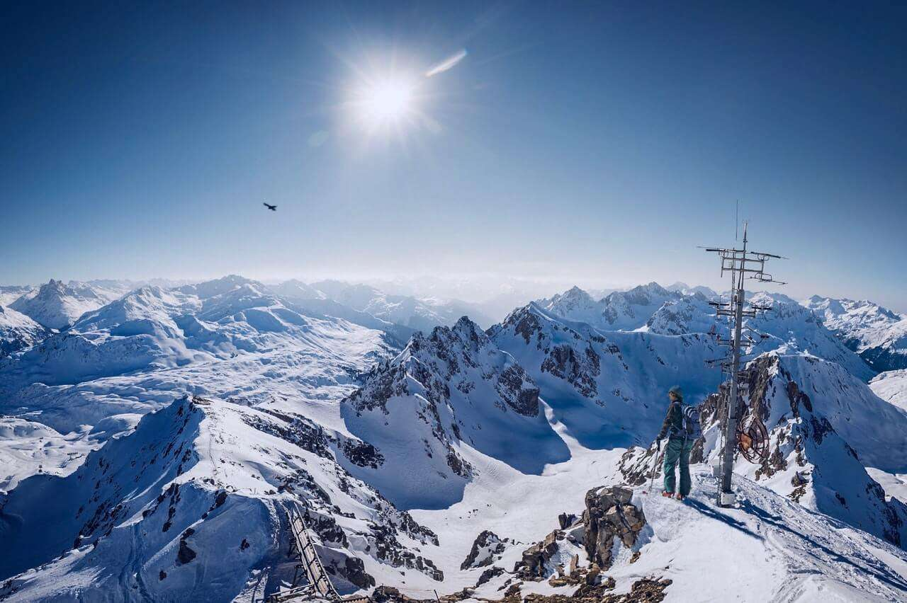 Person on Top of Snow Covered Mountain Under Clear Blue Sky
